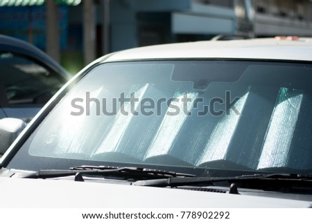 sun shade or sun reflector on the windshield the car Protection of the car in a parking. have the light from the sun shines to the windshield #778902292