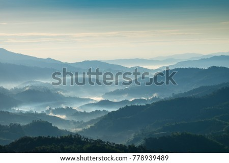 Beautiful Landscape of mountain layer in morning sun ray and winter fog at Chiangrai, Thailand #778939489