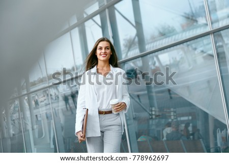 Beautiful Woman Going To Work With Coffee Walking Near Office Building. Portrait Of Successful Business Woman Holding Cup Of Hot Drink In Hand On Her Way To Work On City Street. High Resolution. #778962697