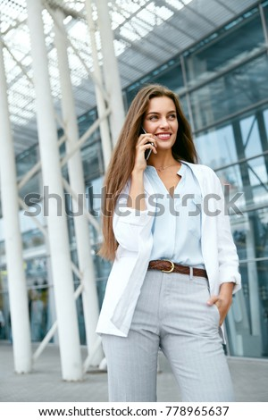 Business Woman With Phone Near Office. Portrait Of Beautiful Smiling Female In Fashion Office Clothes Talking On Phone While Standing Outdoors. Phone Communication. High Quality Image. #778965637