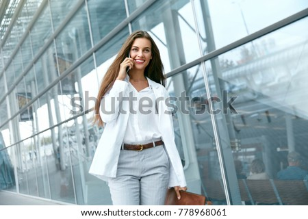Business Woman With Phone Near Office. Portrait Of Beautiful Smiling Female In Fashion Office Clothes Talking On Phone While Standing Outdoors. Phone Communication. High Quality Image. #778968061