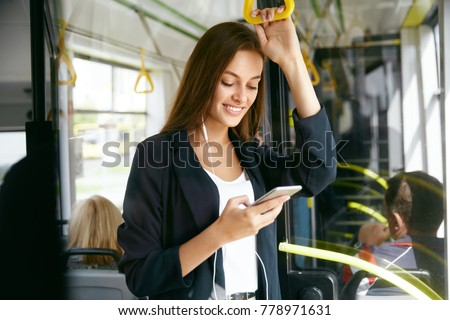 Woman Listening Music On Phone Riding In Bus. Portrait Of Stylish Smiling Girl Listening Music In Headphones, Using Smartphone While Riding In Public Transport. High Resolution. #778971631