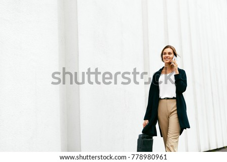 Beautiful Woman Talking On Phone Walking On Street. Portrait Of Stylish Smiling Business Woman In Fashionable Clothes Calling On Mobile Phone Near Office. Female Business Style. High Resolution. Royalty-Free Stock Photo #778980961