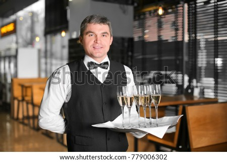 Waiter holding tray with glasses of champagne indoors #779006302
