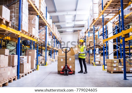 Female warehouse worker loading or unloading boxes. #779024605