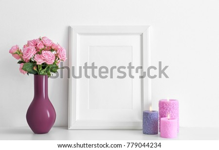 Empty frame, pink roses and candles on table near white wall