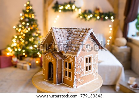 gingerbread house over defocused lights of Chrismtas decorated fir tree #779133343