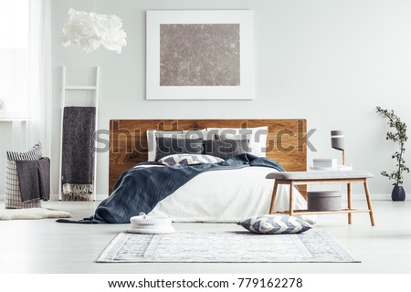 Silver painting on white wall above bed in designer bedroom interior with ladder, lamps and bedsheets #779162278
