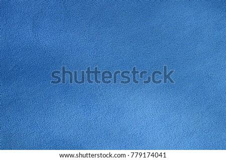 The blanket of furry blue fleece fabric. A background texture of light blue soft plush fleece material #779174041