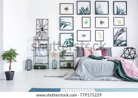 Plant near king-size bed with pink and green bedsheets in modern bedroom with botanic gallery #779175229