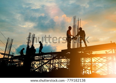 Silhouette of engineer and construction team working at site over blurred background sunset pastel for industry background with Light fair. Royalty-Free Stock Photo #779182138