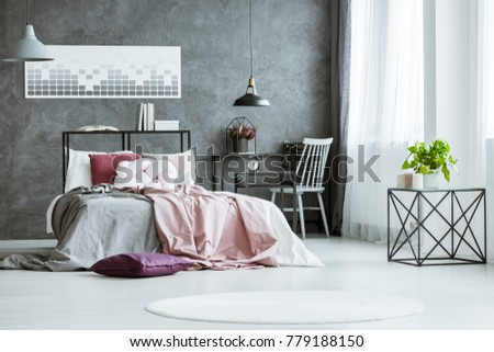 Plant on designer table in bright bedroom with grey and pink bedsheets on bed in bedroom with workspace and poster on wall #779188150