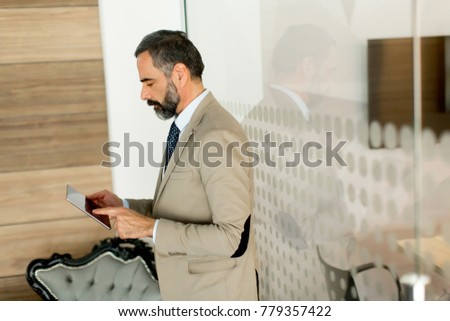 Handsome mature businessman with digital tablet in the office #779357422