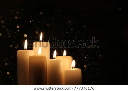 Candles Burning at Night. White Candles Burning in the Dark with lights glow. Focus on six candles in foreground.  #779378176