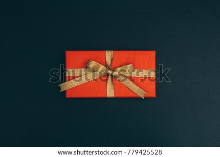 Top view of a red gift box with a gold ribbon on a black table #779425528
