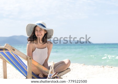 Happy asian woman sitting at the beach have copy space on right handside. relax and travel concept.