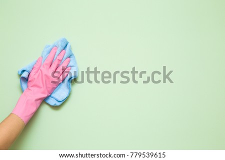 Employee hand in rubber protective glove with micro fiber cloth wiping wall from dust. Maid or housewife cares about house. Spring general or regular clean up. Commercial cleaning company concept. #779539615