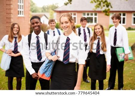 Portrait Of Teenage Students In Uniform Outside School Buildings Royalty-Free Stock Photo #779645404