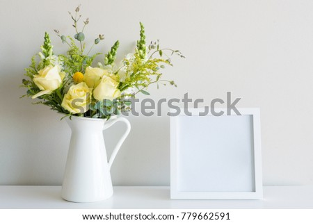 Bouquet including yellow roses in white jug on table with blank square picture frame against neutral background