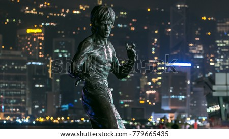 Bruce Lee monument timelapse hyperlapse in the night at the Avenue of stars, modern skyscrapers at the background in Hong Kong. Bruce Lee was  the most influential and famous  martial artist of the 20 #779665435