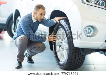 Full length shot of a happy mature man checking out tires of a new automobile at the dealership driving safety seasonal wheels modern technologies automobile vehicle transportation concept #779713291