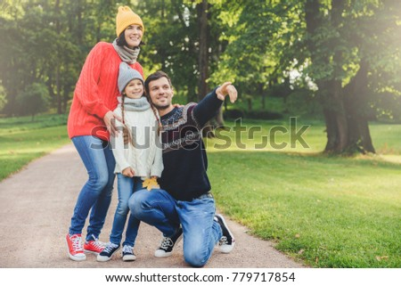 Pleasant looking dad shows with fore finger beautiful landscape to her daughter, embraces her. Family of three members have walk at park, have good relatioship, look into distance as notice something #779717854