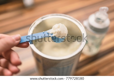 Powder milk and blue spoon on light background close-up. Milk powder for baby in measuring spoon on can. Powdered milk with spoon for baby. Baby Milk Formula and Baby Bottles.  #779728180