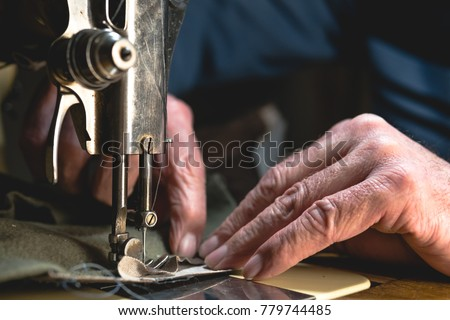 Sewing process of the leather belt. old Man's hands behind sewing. Leather workshop. textile vintage sewing industrial Royalty-Free Stock Photo #779744485