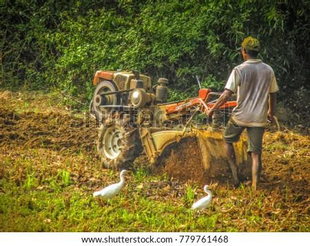 Gokarna Karnataka India December 13-2017 farm worker in the  field with a tractor preparing the soil #779761468