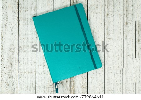Closed bullet journal planner with dotted pages isolated on a white wood background. Concept for New Years Resolutions, or organization Royalty-Free Stock Photo #779864611