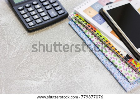 Buseness concept background with a calculator, a mobile phone and a pile of notebooks. Space for your text or product display. #779877076
