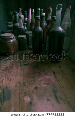 Glass bottles on a stained wooden bench with room for text below underneath. #779955253