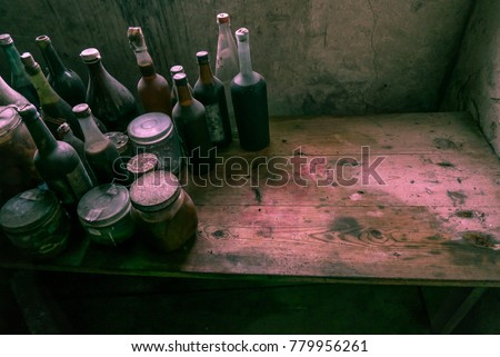 An old and stained bench full of glass bottles. Plenty of room for text. This must be an old witch's kitchen. #779956261
