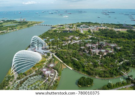 SINGAPORE - NOVEMBER 7, 2017: a panoramic view of the Gardens by the Bay with it's Supertrees and the two famous greenhouses, seen from the Marina Bay Sands Skypark observation deck during the day. #780010375