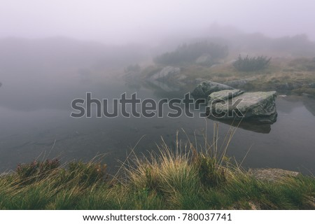 western carpathian mountain tops in  autumn covered in mist or clouds. panoramic view from a distance. mountain lake panorama - vintage film look #780037741