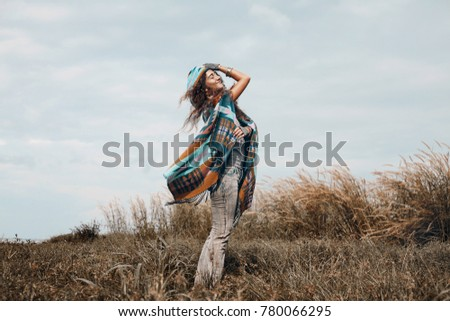 cheerful boho woman wearing poncho on field  #780066295