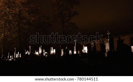 Late night picture of a cemetery/graveyard. Tombstones and crosses are lighted by bright white light. Dark trees are in the background. Low light cemetery picture.