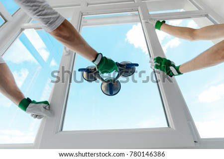 Holding glass with a vacuum lifter. Two guys installing a window in a new building. Construction site, industrial job.