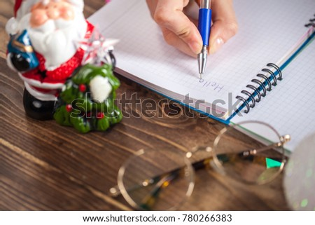 Hands with a pen, notebook and an envelop for letter. A girl is ready to write a letter to Santa Claus. dreams come true, magic holidays and merry Christmas, gifts time #780266383