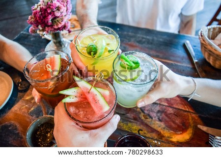 Friends toasting, saying cheers holding tropical blended fruit margaritas.  Watermelon and passionfruit drinks. Royalty-Free Stock Photo #780298633