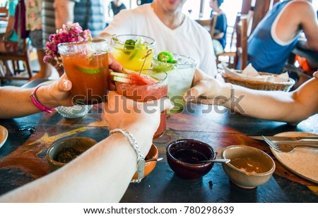 Friends toasting, saying cheers holding tropical blended fruit margaritas.  Watermelon and passionfruit drinks. #780298639