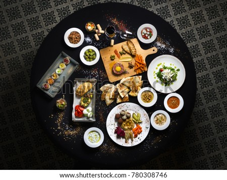 Served round table, Turkish and buckwheat dishes served table top view. Black background. #780308746