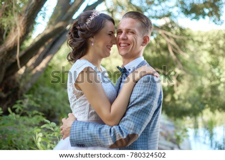The groom holds the bride in her arms near beautiful lake in forest .Wedding couple in love on wedding day #780324502