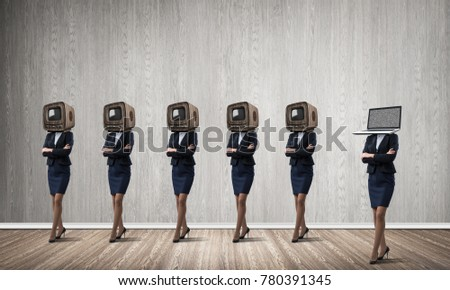 Business women in suits with old TV instead of their heads keeping arms crossed while standing in a row and one at the head with laptop in empty room against gray wall on background. #780391345