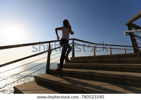 sporty female runner running upstairs on coast trail #780523540