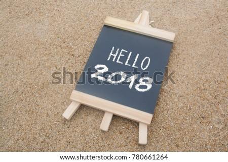 Mini black board written hello 2018 over sand background #780661264