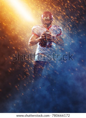 portrait of confident American football player holding ball while standing on the big field with particles effects and lights #780666172
