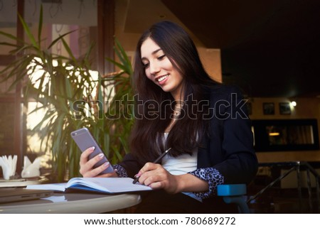Portrait of attractive  happy businesswoman in formal wear checking email on smartphone during work break,  #780689272