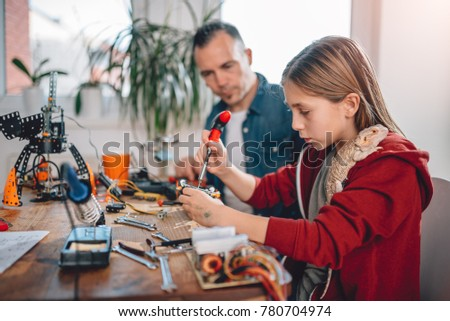 Girl with lizard on shoulder sitting by the wooden table with father and building robot at home at home as a school science project #780704974