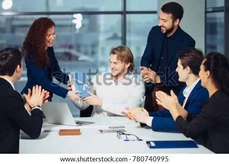 Colleagues celebrating birthday party in office smiling giving presents to boss